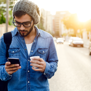 male with beanie holding cup, reading smartphone and walking in street next to parked cars