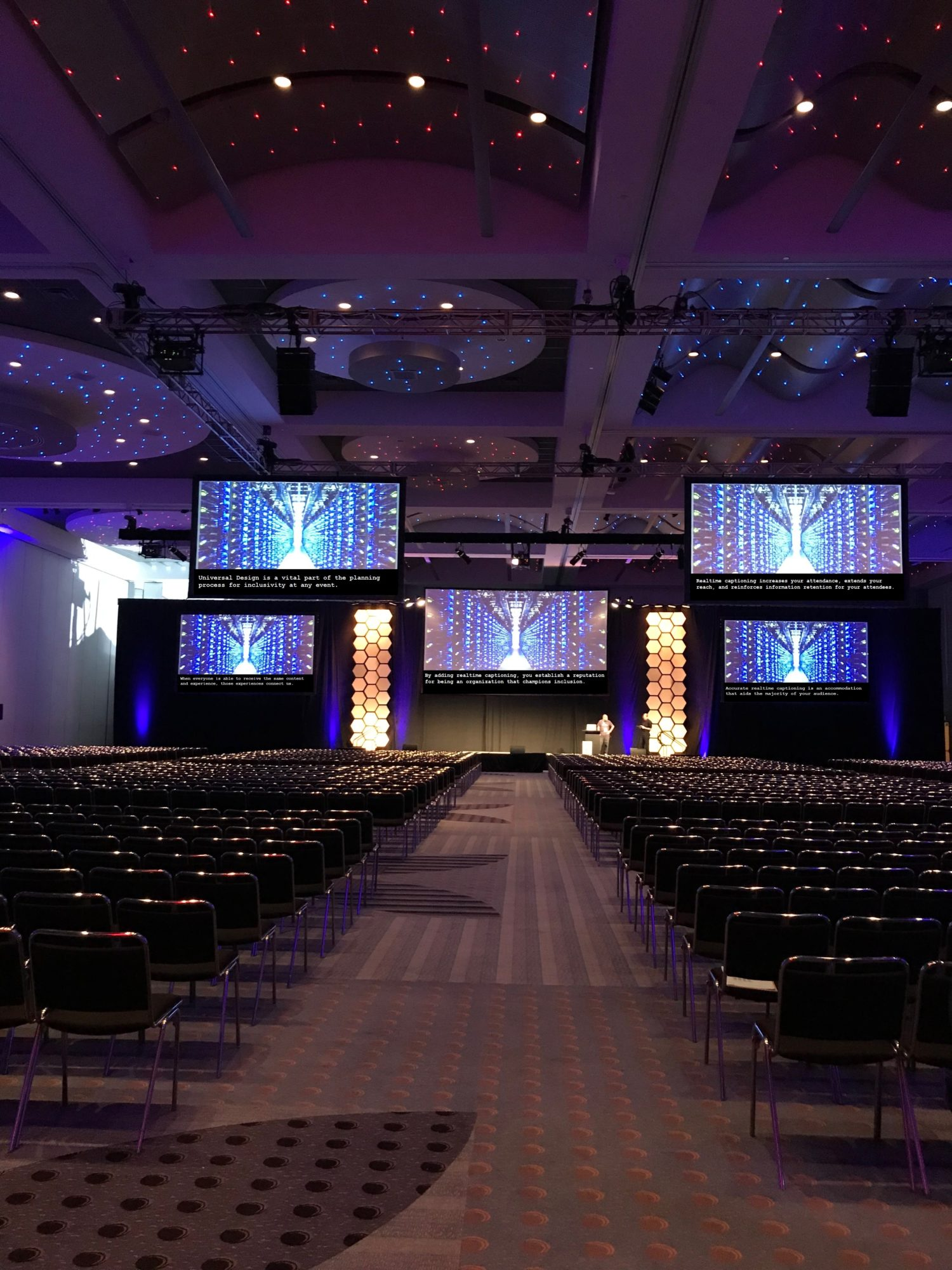 Large ballroom with live conference captioning displayed on the bottom of five jumbo screens.