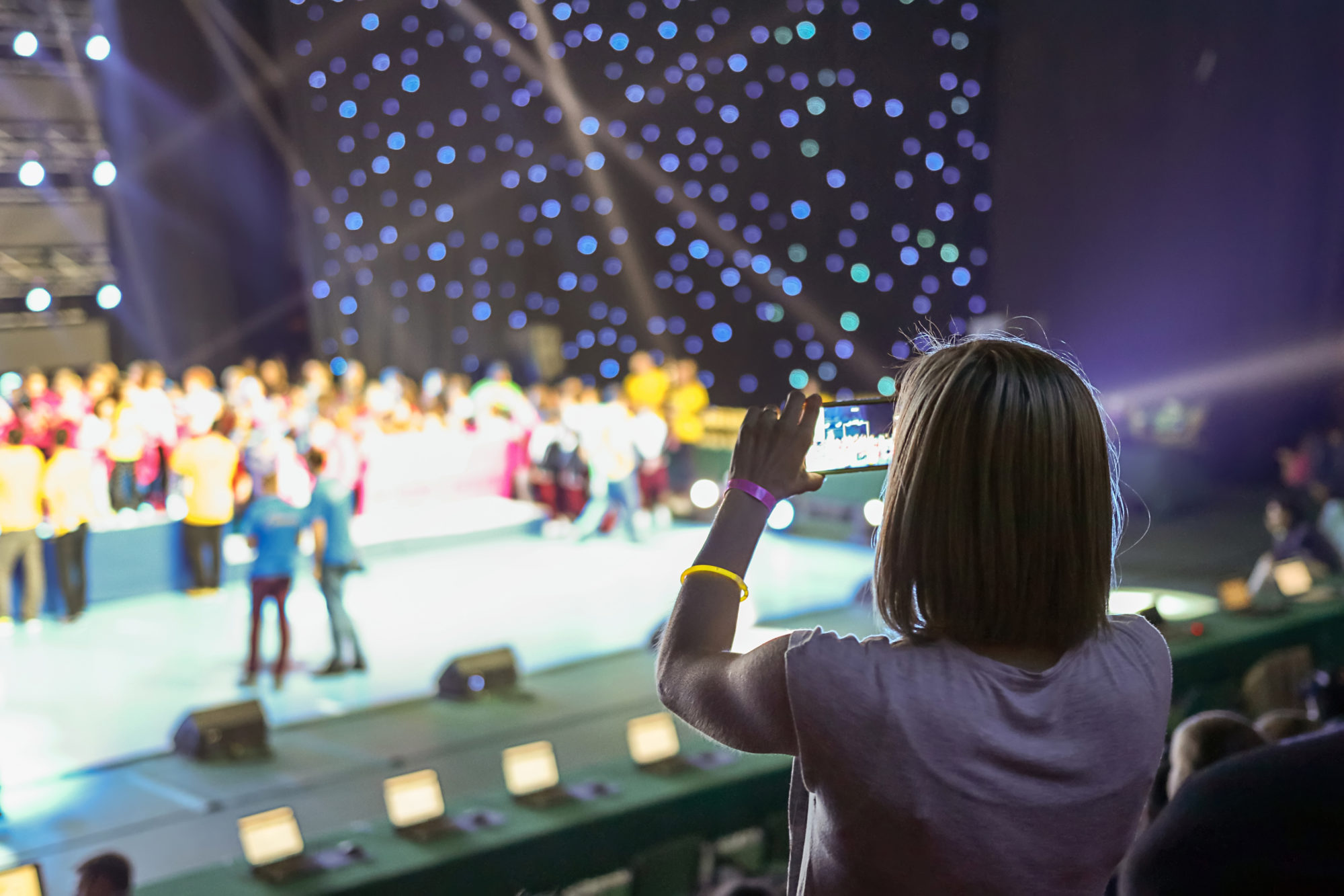 Girl taking picture of stage with smartphone