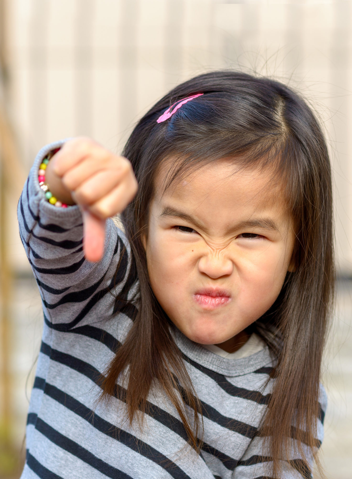 Portrait of a angry little Asian girl giving a thumb down gesture at the camera while pulling a fierce face in a show of childish aggression