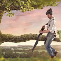A man with a hat is sitting on a branch he is about to cut off.