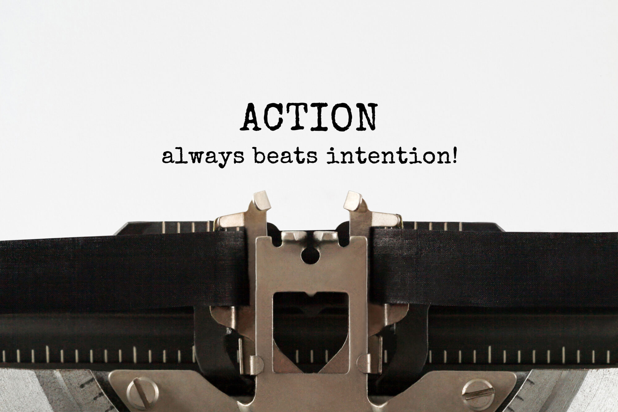 Retro typewriter ribbon with the words the words action always beats intention typed out.