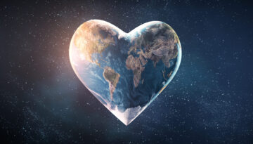 Picture from space of heart-shaped Earth with sunlight shining on the left and stars in the background.